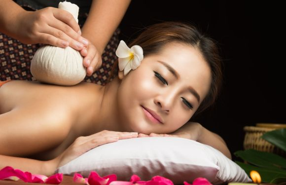 43031260 - asian woman getting thai herbal compress massage in spa.she is very relaxed